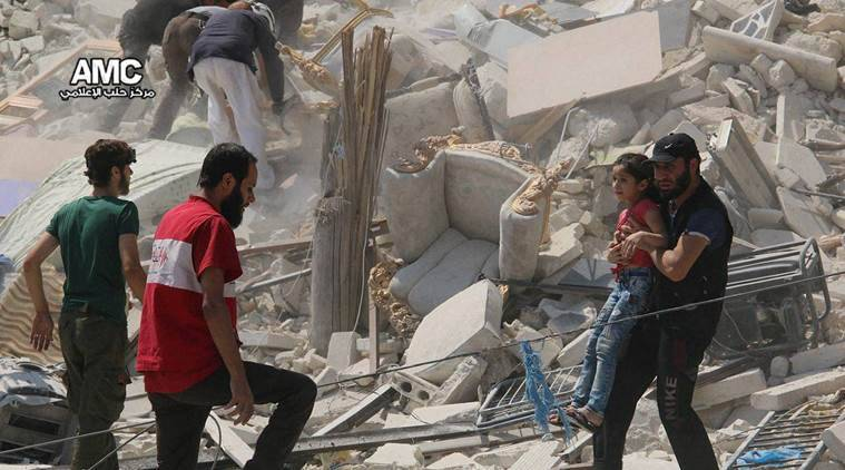 Aleppo : This photo provided by the Syrian anti-government activist group Aleppo Media Center (AMC), shows a Syrian man carrying a girl away from the rubble of a destroyed building after barrel bombs were dropped on the Bab al-Nairab neighborhood in Aleppo, Syria, Saturday, Aug. 27, 2016. Syria activists said, at least 15 civilians have been killed when suspected government helicopters dropped barrel bombs on a wake for children killed in earlier airstrikes in rebel-held Aleppo.AP/PTI(AP8_27_2016_000282B)