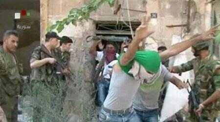 CORRECTION: CORRECTS DATE TO SATURDAY JULY 30, 2016 -- This still image from Syrian state TV video, shows young men with their faces covered surrendering to government forces, in Aleppo, Syria, Saturday, July 30, 2016, Syrian state media is reporting that dozens of families have started leaving besieged rebel-held neighborhoods in the northern city of Aleppo after the government opened safe corridors for civilians and fighters who want to leave. The Russian military says 169 civilians have left through the corridors since they were set up, but Syrian opposition activists say no civilians have left besieged parts of the city. (Syrian State TV, via AP)