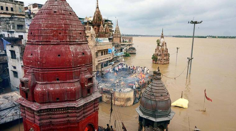 Cremations being performed on the roof a building as the famous Manikarnika Ghat is seen flooded in Varanasi on Monday. PTI Photo (PTI8_22_2016_000289B)