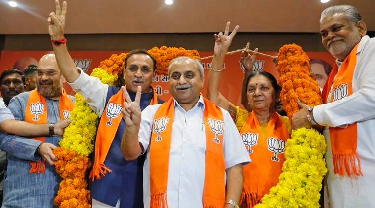 Vijay Rupani, second left, state president of Bharatiya Janata Party (BJP) in Gujarat, is garlanded as he is selected as Chief Minister of the state, along with Nitin Patel, third left, in Gandhinagar, India, Friday, Aug. 5, 2016. Patel will take over as Deputy Chief Minister. (AP Photo/Ajit Solanki)