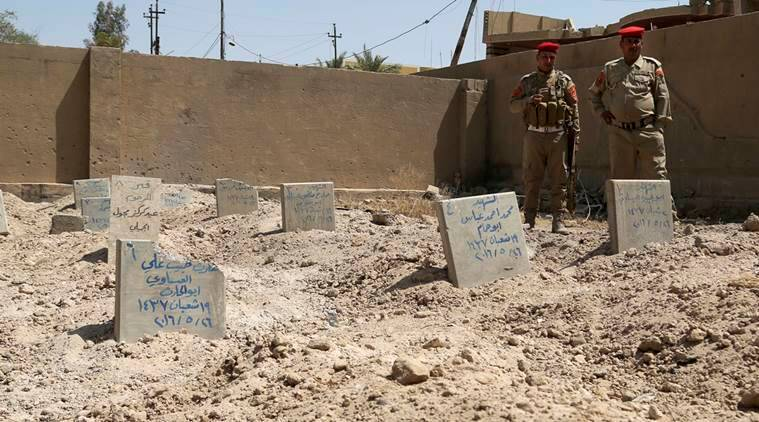 Iraqi security forces inspect a school yard used as a cemetery for killed Islamic State group fighters in Fallujah, 40 miles (65 kilometers) west of Baghdad, Iraq. (AP Photo/ Khalid Mohammed)