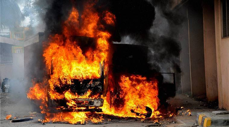 Bengaluru : A vehicle from Tamil Nadu in flames after it was torched by pro-Kannada activists during a protest over Cauvery water row, in Bengaluru on Monday. PTI Photo  (PTI9_12_2016_000260A)