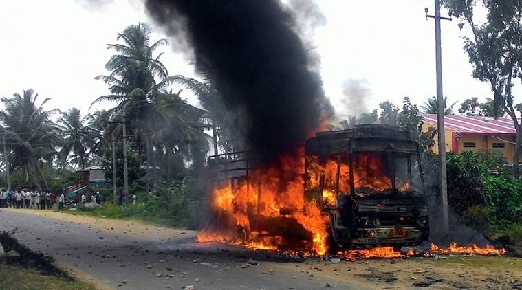 Mandya : A vehicle in flames after it was torched by pro-Kannada activists during a protest over Cauvery water row, in Mandya district on Monday. PTI Photo (PTI9_12_2016_000309B)