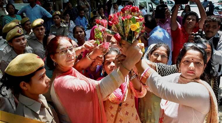 BJP Mahila Morcha workers holding roses  during a protest at Delhi Deputy Chief Minister Manish Sisodia's residence against sacked minister Sandeep Kumar who is involved in sex scandal, in New Delhi on Monday. PTI Photo