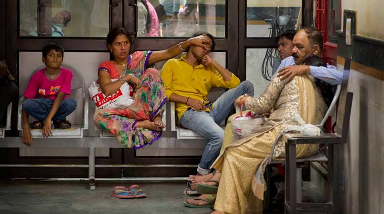 People suffering from high fever sit with their relatives to see a doctor at a fever clinic at Ram Manohar Lohia hospital in New Delhi, India, Tuesday, Sept. 20, 2016. Several cases of mosquito-borne diseases like Chikungunya, Malaria and dengue fever has been reported in the Indian capital over the past weeks. (AP Photo/Manish Swarup)