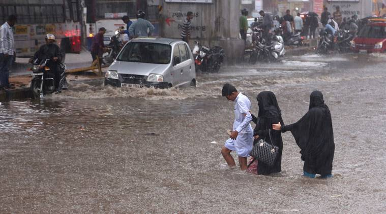 Indians hold on to each other as they cross a flooded street in the rain in Hyderabad, India, Friday, Sept. 16, 2016. Monsoon season in India begins in June and ends in October. (AP Photo/Mahesh Kumar A.)