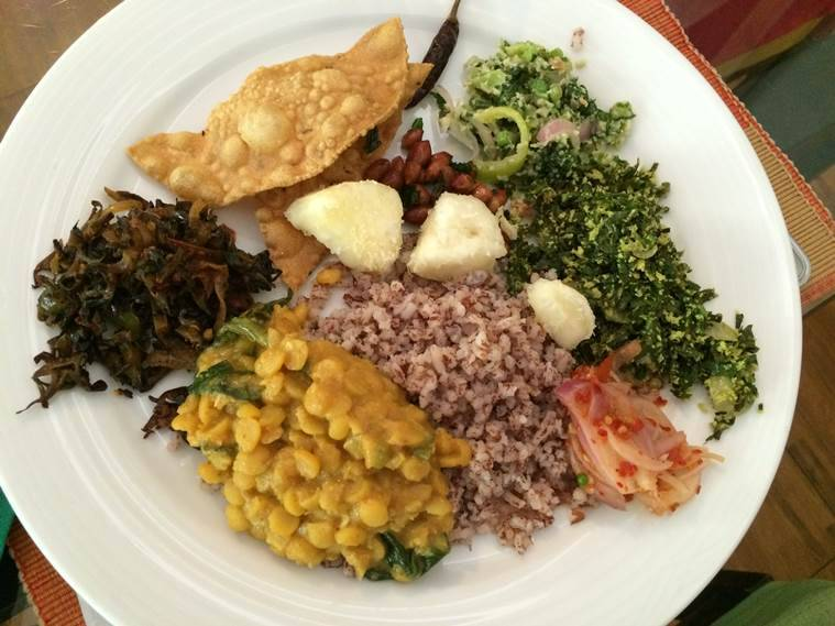 a traditional Sri Lankan meal of dhal, red rice, mallum, a stir fry made of wild leafy vegetables, tapioca and sambol, a fresh coconut chutney
