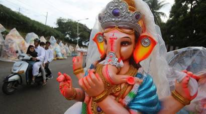 An Indian Muslim family rides past an idol of elephant-headed Hindu god Ganesha, put up on display to be sold ahead of Ganesh Chaturthi festival in Bangalore, India, Friday, Sept. 2, 2016. After worshipping the idols in their homes or specially set up worship venues, devotees immerse them in water bodies at the end of the festival. (AP Photo/Aijaz Rahi)