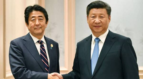Chinese President Xi Jinping, right, and Japanese Prime Minister Shinzo Abe shake hands before their bilateral meeting, on the sideline of the G-20 Summit in Hangzhou. (Kyodo News via AP)
