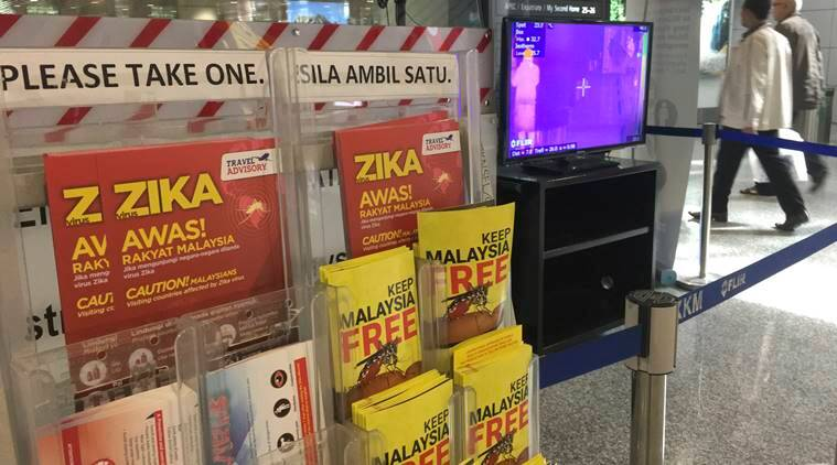 People walk past a travel advisory on the Zika virus infection in Kuala Lumpur International Airport in Sepang, Malaysia, Sunday, Aug. 28, 2016. According to local reports, Singapore Ministry of Health (MOH) and National Environment Agency informed a Malaysian woman living in Singapore became the first patient to be infected by locally-transmitted Zika virus. (AP Photo/Vincent Thian)
