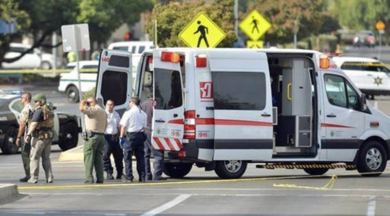 Fresno County sheriff's deputies and Fresno police officers stand on scene near an ambulance after reports of an active shooter in the main lobby of the Fresno County Jail in downtown Fresno, Calif., Saturday, Sept. 3, 2016. Two unarmed officers were critically injured after being shot by a visitor in the lobby of the central California jail, authorities said Saturday. Officers from the secured areas inside the jail ran to the lobby, where a lieutenant fired shots at the gunman, identified as 37-year-old Thong Vang, who was taken into custody. (Silvia Flores/The Fresno Bee via AP)