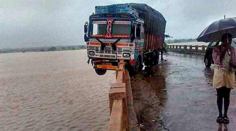 Medak: A truck hangs mid-air after breaking the railing of a road bridge over Manjira river in Medak on Saturday. PTI Photo(PTI9_24_2016_000087A) *** Local Caption ***