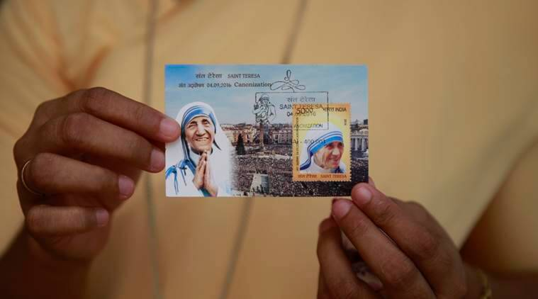 An Indian Christian displays a commemorative postage stamp of Mother Teresa after its release function in Mumbai, India, Sunday, Sept. 4, 2016. Pope Francis declared Mother Teresa a saint on Sunday, honoring the tiny nun who cared for the world's most destitute and holding her up as a model for a Catholic Church that goes to the peripheries to find poor, wounded souls. (AP Photo/Rafiq Maqbool)