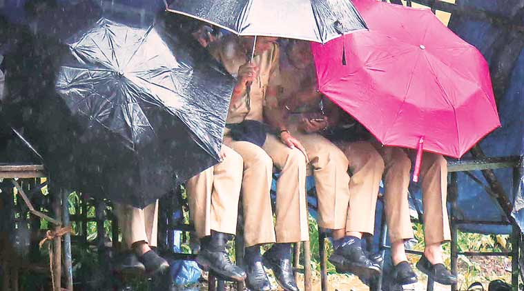 Police officers take shelter from rain under a tent put up by protestors at Azad Maidan  on Tuesday. (Express Photo by Nirmal Harindran)
