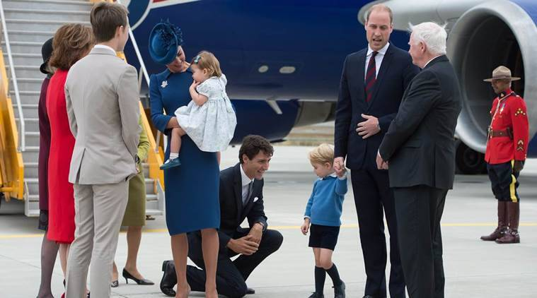 Canadian Prime Minister Justin Trudeau, center, kneels to talk to Prince George as his father, Prince William, The Duke of Cambridge, speaks with Governor General David Johnston, right, and Kate, The Duchess of Cambridge, holds their daughter Princess Charlotte upon arrival in Victoria, British Columbia, Saturday, Sept. 24, 2016. (Jonathan Hayward/The Canadian Press via AP)