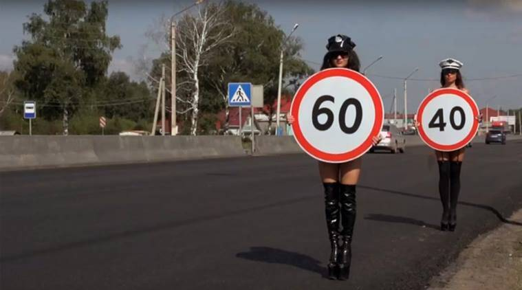 The topless women held signs warning of 60 and 40 kilometres per hour and paraded along a pedestrian crossing. (Source: YouTube)