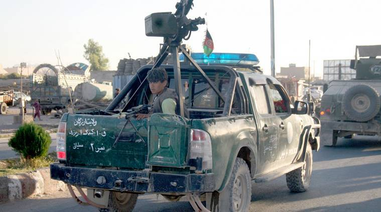 An Afghan policeman travels in the back of a truck in Tirin Kot, the capital of Uruzgan province southern of Kabul, Afghanistan, Thursday, Sept. 8, 2016. The Taliban pushed into the capital of Afghanistan's southern Uruzgan province on Thursday, triggering fierce clashes and sending all government officials fleeing from the city, an Afghan official said. (AP Photo)