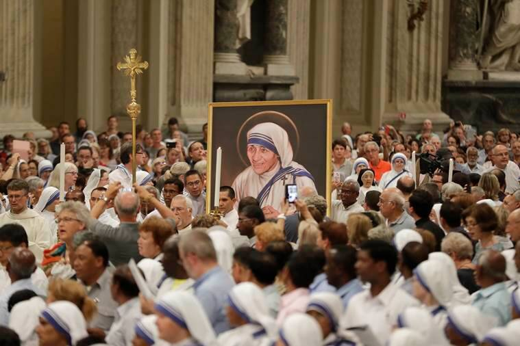 A portrait of Mother Teresa is carried in the crowd during a vigil of prayer in preparation for the canonization of Mother Teresa in the St. John in Latheran Basilica at the Vatican, Friday, Sept. 2, 2016. (AP Photo/Gregorio Borgia)