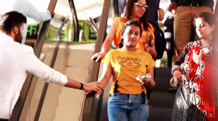 man touches hands of random strangers, people react to random stranger touching them, funny reactions of people startled by man touching their hand, funny youtube videos, funny videos online, indian express, indian express news