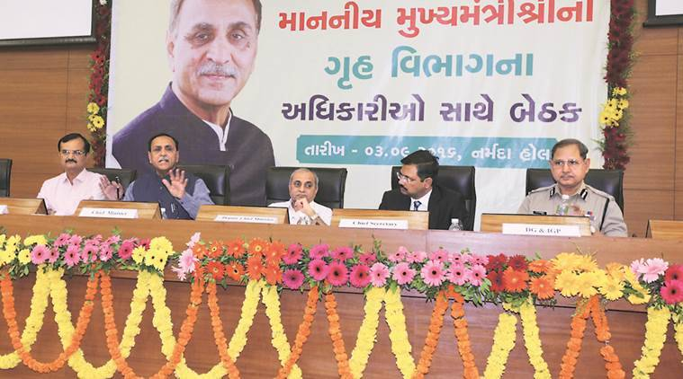 CM Vijay Rupani addresses a gathering of police and home department officials. Deputy CM Nitin Patel and MoS (Home) Pradipsinh Jadeja are also seen.  Express Photo by Javed Raja