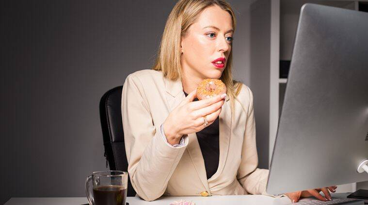 Woman in office eating junk food (Source: Thinkstock images)
