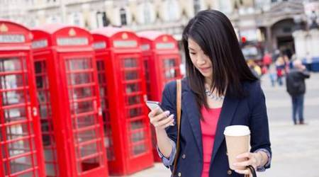 chinese girl in london checking her phone with a coffee