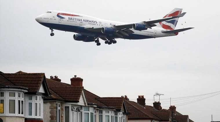 A plane approaches landing over the rooftops of nearby houses at Heathrow Airport in London, Tuesday, Oct. 25, 2016. Britain's government will reveal how it plans to expand London's airport capacity, more than a year after a special commission recommended a third runway at Heathrow. (AP Photo/Frank Augstein)