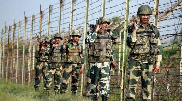 Border Security Force (BSF) personnel patrol along the fence at International Border in RS Pura Sector in Jammu on Wednesday. (PTI Photo)