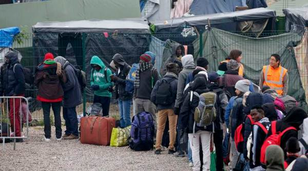 "Migrants with their belongings queue at the start of their evacuation and transfer to reception centers in France, and the dismantlement of the camp called the ""Jungle"" in Calais, France, October 24, 2016.  REUTERS/Pascal Rossignol"