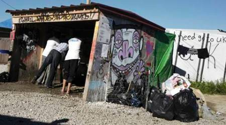 FILE - In this Aug. 23, 2016 file photo, migrants use a lavatory at a makeshift camp in Calais, northern France. Charities operating in Calais are opposing the planned dismantling of the border refugee camp on the French side of the English Channel. Although no official date has been set for the closure of the slum-like camp, the French government has announced it will shut it by the end of the year. (AP Photo/Michel Spingler, File)