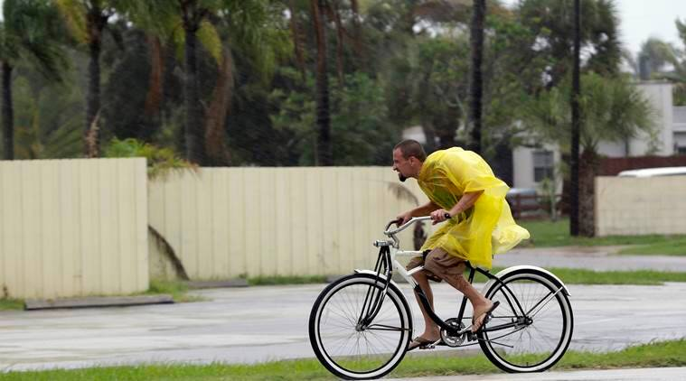 A bicycle rider makes his way through rain Thursday, Oct. 6, 2016, in Cape Canaveral, Fla., as Hurricane Matthew continues to churn its way toward Florida's east coast., (AP Photo/John Raoux)