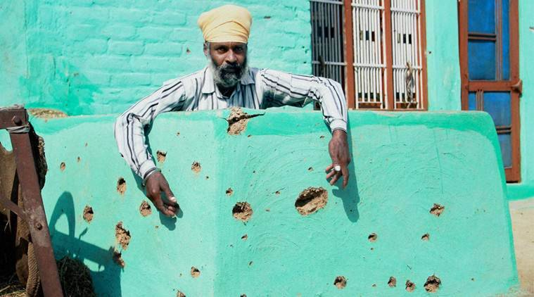 Jammu: A villager shows the pockmarked wall of a building damaged by alleged shelling from the Pakistani side of the border, at Gopad basti village in R S Pura Sector, about 35KM from Jammu, on Thursday. PTI Photo (PTI10_27_2016_000103B)