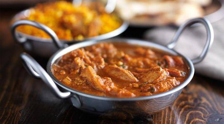 indian butter chicken curry in balti dish with naan bread in background