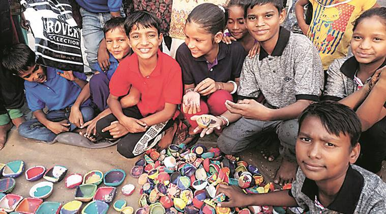 The children have already made around 500 diyas and sell them for Rs 5 per piece. The money collected will be used to buy their sweaters, shoes and socks for winter.  (Express Photo)