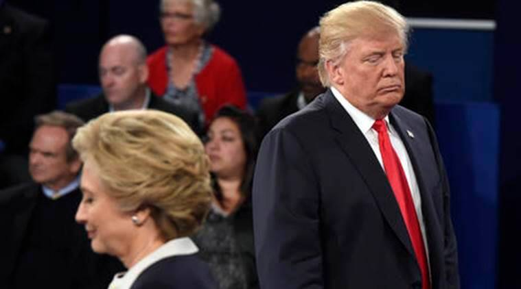 Republican presidential nominee Donald Trump, right, and Democratic presidential nominee Hillary Clinton listen to a question during the second presidential debate at Washington University in St. Louis, Sunday, Oct. 9, 2016. (Saul Loeb/Pool via AP)