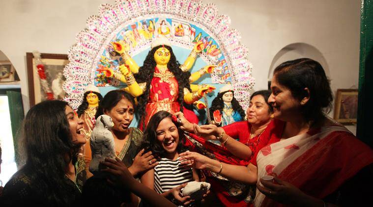The homecoming: Family members crowd in front of the Durga idol at the Chatterjee home in Chorbagan. (Source: Express photo by Partha Paul)