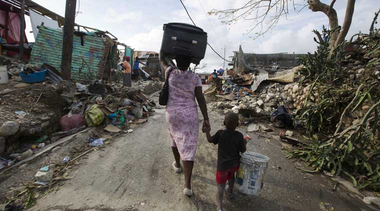 A woman walks to a shelter with her son as they leave after their home was destroyed by Hurricane Matthew in Jeremie, Haiti on Sunday, Oct. 9, 2016. (AP Photo)