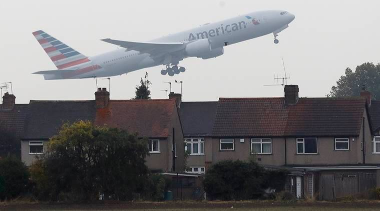 An airplane takes off over the rooftops of nearby houses at Heathrow Airport in Harmondsworth, London, Tuesday, Oct. 25, 2016. Britain's government gave the go-ahead Tuesday to build a new runway at London's Heathrow airport despite concerns about air pollution, noise and the destruction of homes in the capital's densely populated western neighborhoods. (AP Photo/Frank Augstein)