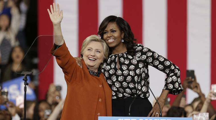 Democratic presidential candidate Hillary Clinton, accompanied by first lady Michelle Obama, greet supporters during a campaign rally in Winston-Salem. (AP Photo)