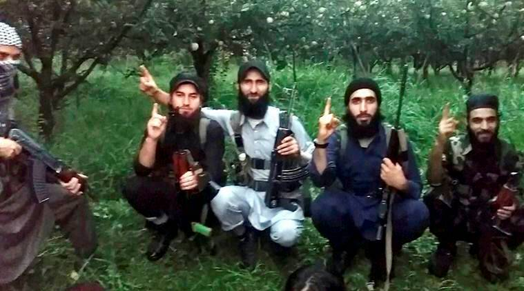 Srinagar: A group of Hizbul militants displaying weapons snatched from the J & K security forces in an orchard in south Kashmir. PTI Photo (PTI10_19_2016_000308B)