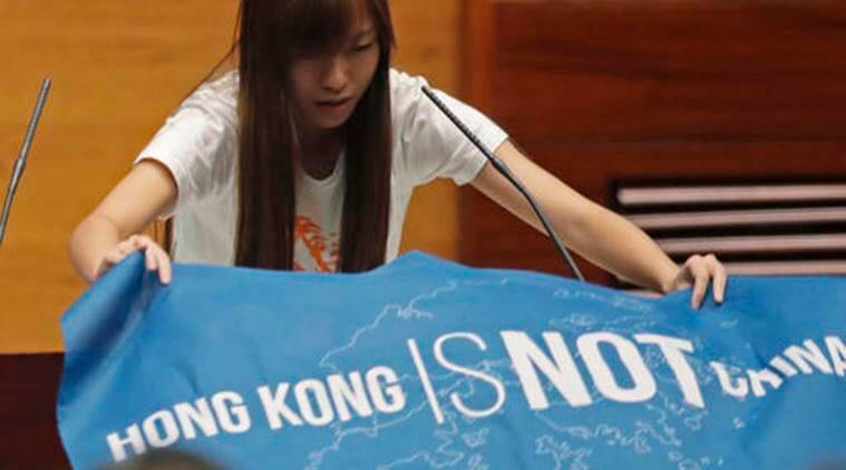 "A newly elected lawmaker, Youngspiration's Yau Wai-ching displays a banner with words reading ""Hong Kong is not China"" as she takes oath in the new legislature Council in Hong Kong, Wednesday, Oct. 12, 2016. Newly elected Hong Kong pro-democracy lawmakers have thumbed their noses at Beijing at a swearing-in ceremony to start the legislative session. They displayed flags declaring that Hong Kong is not a part of China and called out for ""democratic self-determination"" for the semiautonomous Chinese city at Wednesday's oath taking session. (AP Photo/Kin Cheung)"