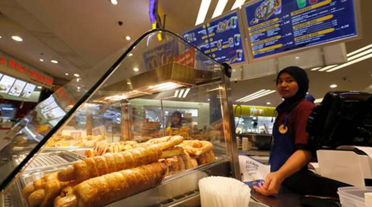 In this Tuesday, Oct. 18, 2016 photo, Pretzel Dogs are on display at Auntie Anne's at a shopping mall in Kuala Lumpur, Malaysia. Hot dogs, or at least the name, will soon be off the menu for a U.S. fast food chain selling the popular snack in Malaysia. The chain, Auntie Anne's, has been told by Islamic authorities that its popular Pretzel Dog, which contains no dog meat, has to be renamed as it is confusing for Muslim consumers. (AP Photo/Vincent Thian)