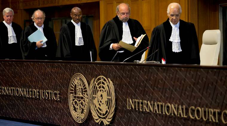 Judges, with presiding judge Ronny Abraham of France, second right, re-enter the World Court in The Hague, Netherlands, Wednesday, Oct. 5, 2016 to read the verdict in the case of the Marshall Island versus Pakistan. The Marshall Island are taking India, Pakistan and the U.K. to court to urge those powers to resume negotiations to eradicate the world's nuclear stockpile, three separate rulings were handed down. (AP Photo/Peter Dejong)
