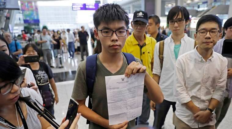 Hong Kong pro-democracy activist Joshua Wong, center, shows the letter from Thailand Immigration office after arriving at Hong Kong airport from Bangkok, Wednesday, Oct. 5, 2016. Thailand stopped teen pro-democracy activist Wong from entering the country and sent him back to Hong Kong, officials said Wednesday, in a move supporters suspected was triggered by pressure from Beijing. (AP Photo/Kin Cheung)