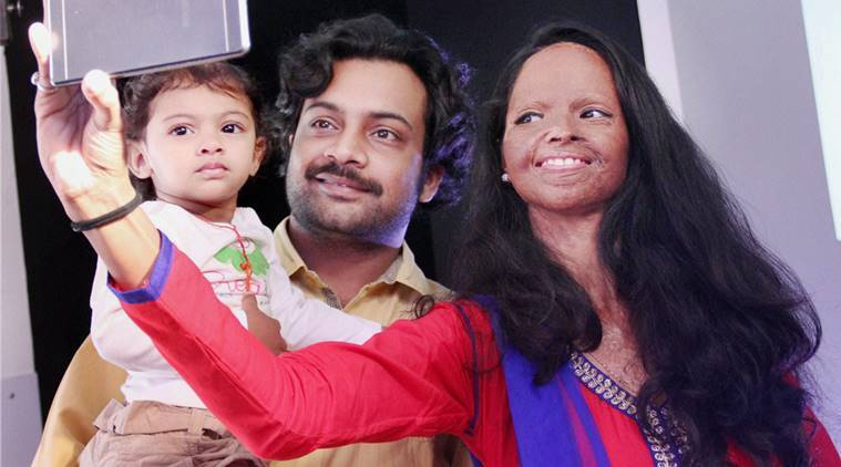 Gurgaon:  Acid attack victim Laxmi clicks a selfie with her husband and child at Diversity Awareness Month organised by Erricson  in Gurgaon on Wednesday. PTI Photo(PTI10_19_2016_000122B)