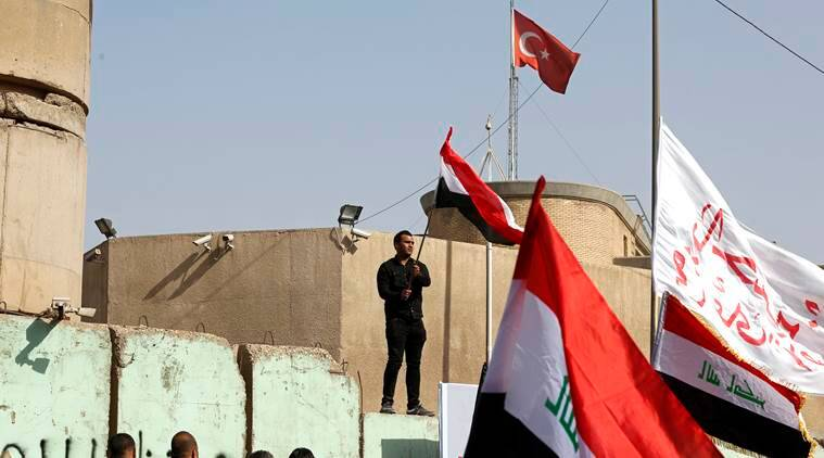Supporters of Shiite cleric Muqtada al-Sadr wave national flags during a demonstration in front of the Turkish Embassy calling for the immediate withdrawal of Turkish troops from northern Iraq, in Baghdad, Iraq, Tuesday, Oct. 18, 2016. Thousands of followers of al-Sadr are marching in front of the Turkish Embassy in Baghdad, demanding the withdrawal of Turkish troops from a base near the northern city of Mosul. Turkey says the troops are training Iraqi fighters to help retake Mosul from the Islamic State group, and that they are there with the permission of the Iraqi government. Baghdad denies it granted permission and has ordered them to withdraw -- a call Ankara has ignored. (AP Photo/Karim Kadim)