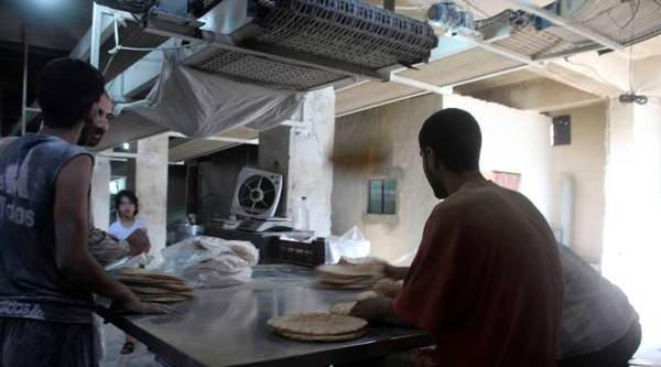 In this photo taken Oct. 1, 2016 and provided by the local council of Aleppo city, Syrians bakers make bread at a bakery, in Aleppo, Syria. The opposition-held districts of the Syrian city have been surrounded and under siege for months. Russian and Syrian warplanes are bombing the streets into rubble and government forces are chipping away at the pocket of opposition control. (Local Council of Aleppo City via AP)