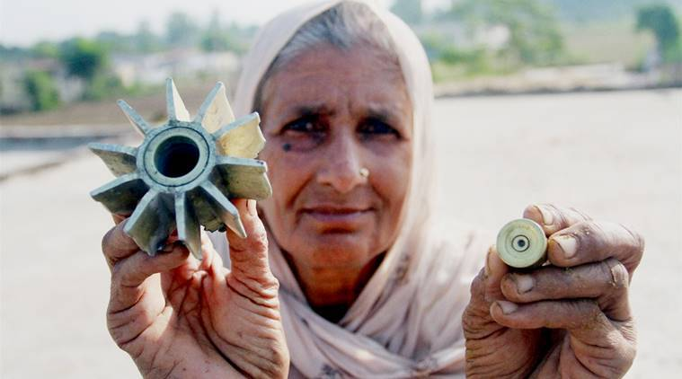 Jammu: A woman shows parts of mortar shell allegedly fired from Pakistan's side in Korotana Khurd village of RS Pura sector, about 27km from Jammu, on Saturday. PTI Photo (PTI10_22_2016_000060A)