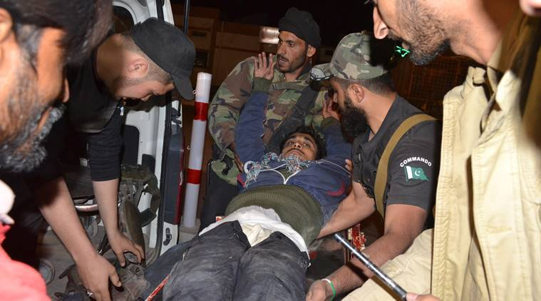 Pakistani volunteers and police officers rush an injured person to a hospital in Quetta, Pakistan, Monday, Oct. 24, 2016, after two separate attacks in Pakistan. Gunmen stormed a police training center in the restive southwestern province of Baluchistan Monday, leaving several people wounded, hours after another attack near to Quetta leaving two customs officers dead, authorities said. (AP Photo/Arshad Butt)