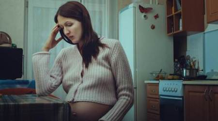 Sad pregnant woman sitting in the kitchen.  She's in a bad mood.